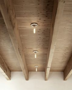 A plywood ceiling accented with raw ceramic based bulbs.