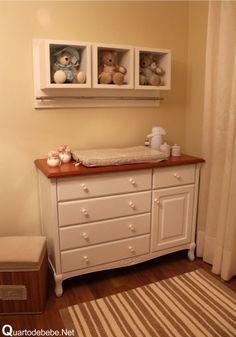 cômoda branca com bancada de madeira em um quarto de bebê com piso de madeira