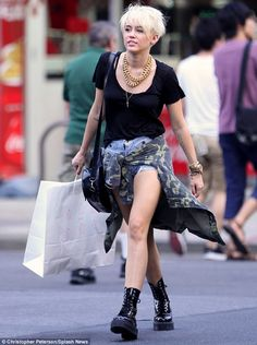 Going grunge: Miley Cyrus stomped around Manhattan on Thursday in combat boots and tattered denim shorts