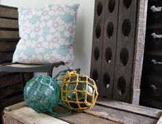 love the rustic textures between the vintage buoys, wine rack and the lush linen #cushion. #textiles