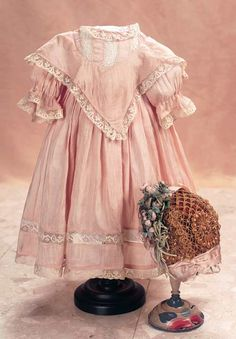 Delicate rose silk dress with bertha collar and woven rosebud bonnet. The yoke bodice is overlaid with a v-shaped bertha collar. The dress has very full skirt and sleeves. There are alternating bands of lace and silk at the yoke, and lace edges the neckline, collar, sleeves, and hem. The lattice straw bonnet is decorated with rose silk bows and generous clusters of tiny silk rosebuds and leaves. Circa 1888.