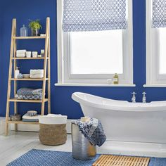 Ocean-blue bathroom with ladder storage unit and patterned blinds
