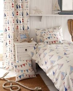 Fryetts - Fryetts Fabric Collection - Sailboat print bedding with bunting print cushions and curtains printed with lighthouses and boats, by a cream bedside table
