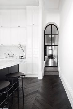 Behind an elegant Victorian facade in Prahran, this chic renovation creates a refined living space for a young family. Infused with classic Parisian style, the finely detailed kitchen became a hub for the family's day-to-day activities, with every element configured to maximise functionality. Banks of white joinery rise up to meet high ceilings while a central island bench with a Carrara marble top accommodates food preparation and informal dining. Minimalist furniture in shades of grey and…
