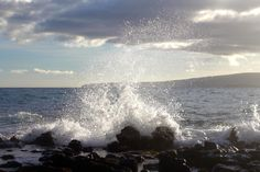 Sea water crashes against black rocks at the Wailea Beach Resort in Maui