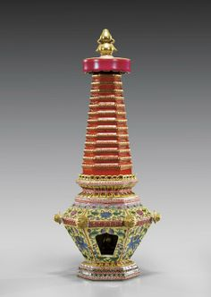 """YONGZHENG-STYLE FAMILLE ROSE PORCELAIN PAGODA Chinese Yonzheng-style Famille Rose enameled, sectional porcelain pagoda; hexagonally shaped, with coral red ribbed spire surmounted with a gilt double-gourd finial; the hollow body decorated with lotus on yellow ground, a gilt deity seated within; seal mark; H: 14"""""""