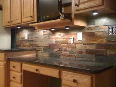 Decorations. Astounding brown grey colors natural stone backsplashes with black color granite countertops and brown color wooden kitchen cabinets and black color metal knobs along with round shape clear downlights. Delightful ideas of kitchen natural stone backsplashes.
