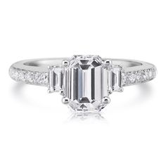 A center emerald cut diamond with side diamond baguettes and pave diamonds going down the shoulders of this platinum ring. Asscher Cut Diamond Engagement Ring, 3 Stone Engagement Rings, Rose Gold Engagement, Emerald Cut Diamonds, Diamond Studs, Forever Brilliant Moissanite, Platinum Ring, Baguette Diamond, Jewelry Stores