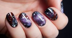 This purple-pink galaxy nail art is accented by glittery stars and freehand flares, and is inspired by the Pelican Nebula.