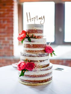 Layered-cake with pink florals and adorable 'Hooray' topper: http://www.stylemepretty.com/new-hampshire-weddings/dover-new-hampshire/2015/08/07/rivermill-new-hampshire-wedding/ | Photography: Ruth Eileen Photography - http://rutheileenphotography.com/