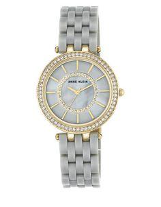 """<ul><li>Mesmerizing watch studded with twinkling Swarovski crystal</li><li>Quartz movement</li><li>Round case, 34mm (1.34"""")</li><li>Mixed metal bezel studded with Swarovski crystals</li><li>Goldtone textured crown</li><li>Gray dial</li><li>Goldtone stick indices</li><li>Second hand</li><li>Plastic bracelet, 16mm (0.63"""")</li>&l..."""