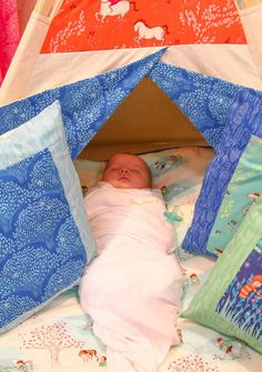 Baby sleeping on a pillow under a tent...that looks like heaven