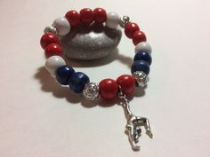 Wear the pride in your favorite gymnast on your wrist with a customized Player Pride Bracelet!  Each beautiful, customized bracelet has a gymnast charm surrounded by beads in your team's colors and & silver lantern beads!