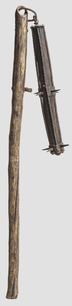 Länglicher, hölzerner Schlagkopf mit eiserner Montierung. Umlaufend zwei Bänder mit je vier Dornen, seitlich tordierte Spangen. Die Enden jeweils mit blütenförmigen Deckplatten abgeschlossen. Einfacher, gewachsener Schaft, die Öse an zwei kräftigen Schaftfedern befestigt, seitlich weitere Ringöse. Schaft vermutlich verkürzt. Gesamtlänge 122 cm. Einfache, aber effektive Bauernwaffe, von der sich nur wenige Exemplare erhalten haben. Selten.  Zustand:II - III