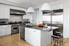 Clean…steel and white kitchen with pendant lighting by Artemide // Victoria Hagan Designs - Architectural Digest