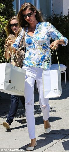 In bloom: The five-foot-11 stunner was wearing a floral blouse, ripped white skinny jeans, and matching bowed flats
