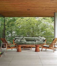 The travertine terrace just beyond the living room has a pair of chairs, coffee table, and sofa by local furniture maker Saccaro. Photo by Matthew Williams.