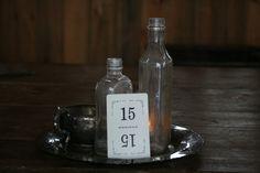 Antique charm. Vintage silver platter and sugar dish. Vintage bottles. Votive candle and holder. Vintage playing card table number. Needs flowers in the vintage bottles, sugar dish, and perhaps a bud on the opposite side. www.facebook.com/...