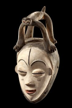 """Okuyi"" mask.Gabon, Punu light brown wood, kaolin, red and black paint, of oval hollowed form, crowned by a stylized quadruped with bulky legs, a a heart-shaped deepened, tapering facial plane, delicate curved brows with raised bean-shaped and narrow-slit eyes below, flanking a short nose with delicate nostrils, a pointed red mouth underneath, scarification marks in the area of forehead and cheeks, min. dam., cracks (quadruped), slight signs of abrasion; variation of the ""white masks of the…"