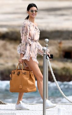 Stylish: The 21-year-old put on a leggy display as she stepped out in a one-shoulder flora...