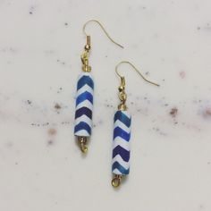 Blue & White Chevron Paper Bead Earrings Show off your personal style with these unique earrings, handcrafted using paper & glass beads! To create these lightweight accessories, I covered paper strips with a vibrant design & hand-rolled each bead. They have been coated with water-resistant (NOT water-proof) varnish. A rain shower shouldn't damage the earrings. However, the beads should not be submerged in water (in a pool, for example). There are small glass beads at the top & bottom of each…