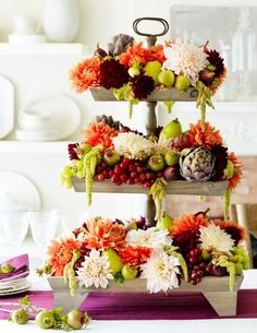 To create this tiered Thanksgiving centerpiece, press dahlias, fruits and vegetables into florists' foam on a tiered fruit basket or cake stand. More Thanksgiving centerpieces: http://www.midwestliving.com/homes/seasonal-decorating/holiday-ideas/easy-thanksgiving-centerpieces/?page=5