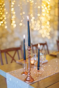 Gold candlesticks, geometric holders and black candles on glitter wedding table runners. http://www.confettidaydreams.com/orchid-wedding/