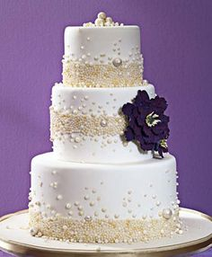 White and ivory pearl wedding cake, accented with a plum/eggplant purple, artificial flower.