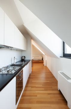 Small galley kitchen in narrow space with sloping ceiling.  Large window in sloped ceiling floods the small space with light.