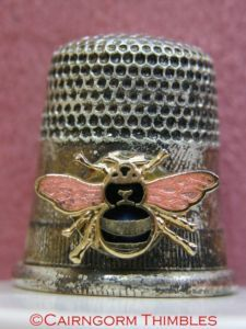 Silver Coloured Metal Thimble Enamel Bee Bumblebee - Bumblebee Thimble This is a silver coloured metal thimble decorated with a rolled rim, a band of vertical striations for gripping a needle, a plain band and then a traditional dimpled design.