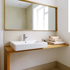Wide mirror with sink and extra counter space with room underneath for built in storage.