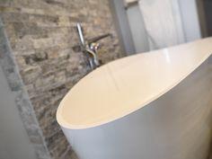 Vrijstaande badkuip met design kraanwerk. Exclusieve producten gecombineerd om ieders badkamer uniek te maken. Accent muur in steen.