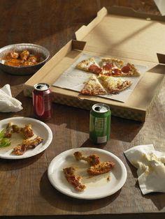 Half-eaten pizza , Buffalo wings and sodas