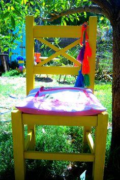 Vestir una silla rústica de colores , con un almohadón patchwork muy shabby chic y unos pompones de lana, para alegrar un sector del jardín, mientras alguien se sienta a disfrutar del aire libre...