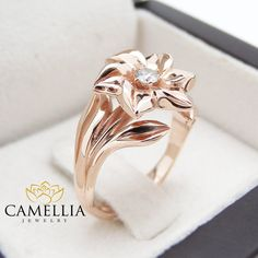 This captivating flower design rose gold engagement ring makes an amazing gift for the woman in your life whether a wife, friend or mother. It features a 14K rose gold leaf encrusted band with an intricately designed 14K rose gold flower with diamond center. This unique ring is the