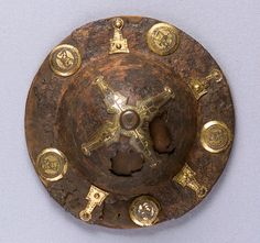 A gold shield boss engraved with simple patterns and Christian symbols, such as fish and crosses. Cast out of iron, with gilt bronze ornamentation. Made in the 500s in Northern Italy for a Lombardic nobleman.  Currently held at the Metropolitan Museum.
