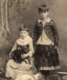 Vintage photo, small dog and two oddly-dressed children.