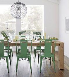 En métal vert, ces chaises donnent de l'allure à la salle à manger en bois.
