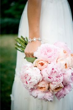 Stunning bouquet made of lush pastel pink peonies and delicate pastel orange roses.