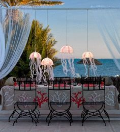 Festive coastal party table with diy jellyfish lamps and coral table covering.