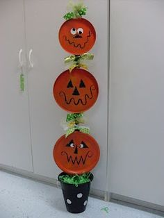 """mollie's mom: """"It's a Pumpkin Totem Pole!!"""" made from dollar store stove covers, yard stick, pail"""