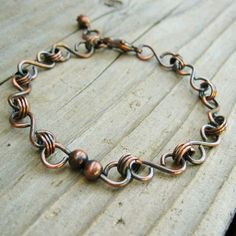 Like the way the beads are added.  Antiqued Copper Charmer bracelet. $18.00, via Etsy.