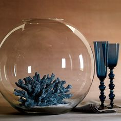 Statement-Making Wedding Centerpiece Idea: Coral nestled in sand and placed in a bubble bowl brings the beach to the table. Faux blue coral, Z Gallerie, zgallerie.com. Bowl, libbey.com. Sand (use two cups per centerpiece), Jamali Garden Supplies, jamaligarden.com. Glasses and napkin, Kim Seybert, kimseybert.com.