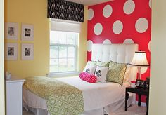 Whimsical girl's bedroom by Emily Clark. Love the bold polka dot accent wall!