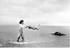 Jacqueline Kennedy swinging Caroline in surf, Hyannis Port, by Mark Shaw 1959