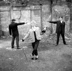 "16-year-old Eileen from Bethnal Green, with two teddy boys ""duelling"" over her on an East End bomb site. 1955 london"