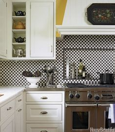 In this retro Chicago kitchen by designer Mick De Giulio, simple one-inch squares of black and white tiles make a graphic backsplash behind the Wolf range. The recessed opening, defined by a pencil detail, acts as a convenient shelf for condiments.