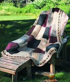 The soft texture and rich colors of Homespun yarn are featured in this exclusive, easy-to-knit patchwork afghan with a unifying ribbon-effect border. (Lion Brand Yarn)