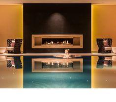 Eine junge Frau badet im Schwimmbad mit Kamin und Ruhebereich des Severin*s Resort und Spa auf Sylt