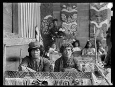 Ngai Tuhoe women weaving taniko borders of cloaks on the mahau (veranda) of Te Whai-a-te-Motu meeting house, Mataatua, Ruatahuna, Urewera region
